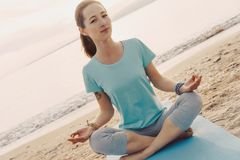 Woman meditating in lotus position on shore. Royalty Free Stock Photography