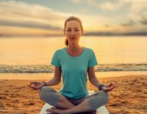 Woman meditating in pose of lotus on yoga mat on beach. Young woman meditating in pose of lotus on yoga mat on sand beach near the sea at sunset in summer stock image