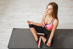 Young woman meditating, practicing yoga. Young woman meditating, top view. Sporty girl practicing yoga, sitting on mat in lotus pose Royalty Free Stock Photo