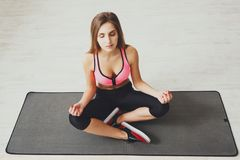 Young woman meditating, practicing yoga. Young woman meditating, top view. Sporty girl practicing yoga, sitting on mat in lotus pose Royalty Free Stock Photography