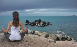 Young woman meditating at the sea coast stock photos