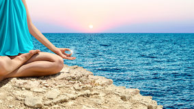 Young woman meditating on the sea shore Stock Photography