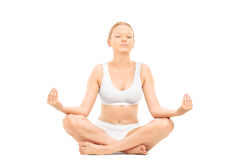 Young woman meditating seated on the floor Stock Photo