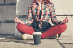 Young woman meditating in the street Stock Images