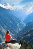 Young woman meditating on top of the mountain Stock Photography