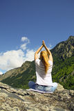 Young woman meditating on top of a mountain Royalty Free Stock Photos