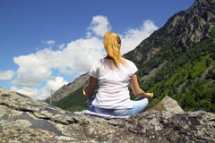 Young woman meditating on top of a mountain Stock Images
