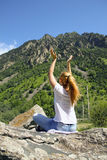 Young woman meditating on top of a mountain Stock Image