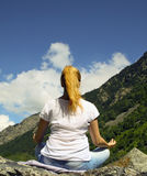 Young woman meditating on top of a mountain Royalty Free Stock Images