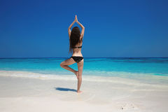 Young Woman meditating in tree yoga position on the exotic beach Stock Image