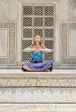 Young woman meditating at the wall of Taj Mahal Stock Photography