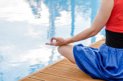 Young woman meditating on a wooden deck. In lotus position Royalty Free Stock Photo