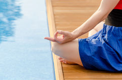Young woman meditating on a wooden deck. In lotus position Stock Images
