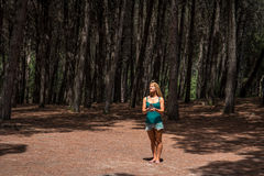 Young woman meditating in the woods. Young woman standing peacefully in the woods with huge cone in hands. Shot in a park of Monte Arci, Oristano province royalty free stock photography