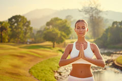 Young woman meditating. Yoga at park with view of the mountains and lake. Young woman with clasped hands. Concept of calm and meditation Royalty Free Stock Photo