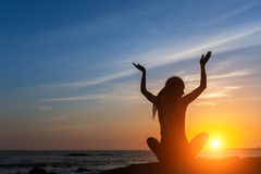 Young woman in a meditating yoga pose overlooking the amazing sunset. Mind body spirit concept Stock Photography