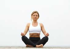Young woman meditating in yoga pose Royalty Free Stock Image