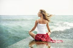 Young woman meditation on the beach Stock Photos
