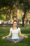 Young woman meditation in city park. Yoga exercise Stock Image