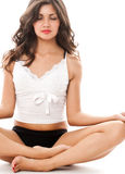 Young woman in meditation pose. Portrait of young sexy woman in meditation pose dressed in underwear isolated on white Stock Photo