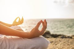 Young woman meditation yoga pose on tropical beach with sunlight. In background stock photos