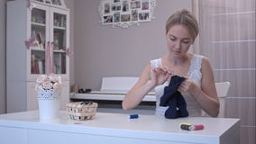 Young woman mending childrens clothes stock footage