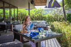 Young woman with menu sitting in outdoor restaurant Royalty Free Stock Photography