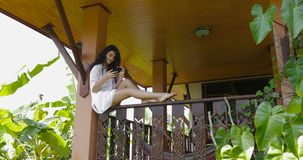 Young woman messaging with cell smart phone sitting on balcony in hotel in tropical forest, beautiful girl chatting stock video footage