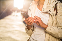 Young woman messaging/using app on her smart-phone. In a city street context (shallow DOF; color toned image Stock Photos