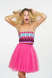 Young woman with messed up hair. Attractive young woman in fancy pink dress got her hair messed up Stock Images