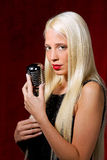 Young woman with a microphone as a singer. In evening gown royalty free stock images