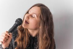 Young woman with a microphone in hands royalty free stock image