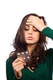 Young woman with migraine, holding pills Royalty Free Stock Photography