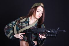 Young woman in the military uniform with the assault rifle Stock Images