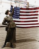 Young woman in military uniform holding up an American flag Royalty Free Stock Photography