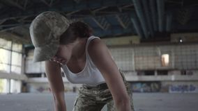 Confident young woman in military uniform training in dusty dirty abandoned building. Slim girl running up to the camera. Young woman in military uniform stock footage
