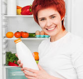 Woman against the refrigerator Royalty Free Stock Photo