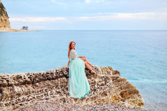 A young woman in a mint dress sits on a large stone on the shore of the Adriatic Sea Royalty Free Stock Photos