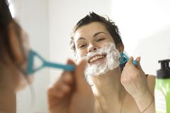 Young woman at the mirror shaving royalty free stock photography
