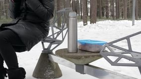 Young woman in mittens pours hot tea in a cup from a thermos outside in winter time. stock video footage