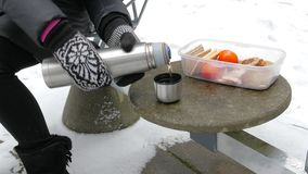 Young woman in mittens pours hot tea in a cup from a thermos outside in winter time. stock footage