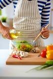 Young woman mixing fresh salad Royalty Free Stock Photo