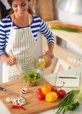 Young woman mixing fresh salad Stock Image