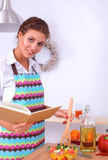 Young woman mixing fresh salad standing near desk Stock Photo