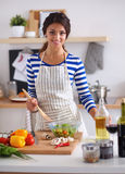 Young woman mixing fresh salad, standing near desk Royalty Free Stock Photos