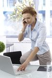 Young woman on mobile in office Stock Photo