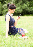 Young woman with mobile in the park Stock Photography