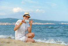 Young woman with mobile phone. On a beach Royalty Free Stock Photography