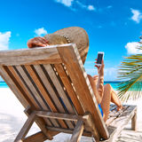 Young woman with mobile phone at the beach Stock Photo