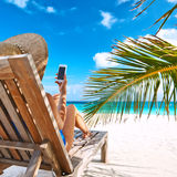 Young woman with mobile phone at the beach Royalty Free Stock Images